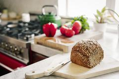 A fresh loaf of baked brown bread on a board with a breadknife. Stock Photos