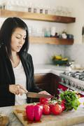 A woman using a sharp knife, slicing tomatoes. Stock Photos