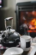 A home hearth, a lit fire and a table with a teapot and coffee Stock Photos