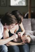 A same sex couple, two women playing with their 6 month old baby girl. Stock Photos