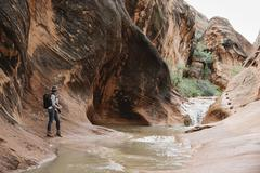 Woman standing by river in a canyon. Stock Photos