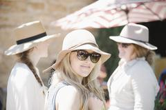 Portrait of three women wearing hats and sunglasses. Stock Photos