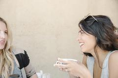 Woman with long brown hair holding a cup, chatting to a friend. Stock Photos