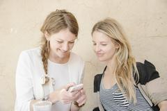 Two smiling women sitting at a table, looking at a cell phone. Stock Photos