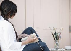 Young woman with long brown hair, holding a sketch book and paint brush. Stock Photos