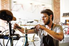 A man working in a bicycle repair shop, checking the frame of the bike. Stock Photos