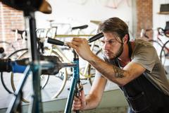 A man working in a bicycle repair shop, checking the frame of the bike. Kuvituskuvat