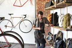 A man working in a bicycle repair shop looking at his smart phone. Stock Photos