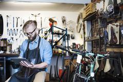 A man working in a bicycle repair shop, seated using a digital tablet. Stock Photos