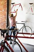 A man working in a bicycle repair shop. Stock Photos