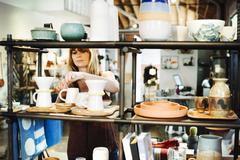 Woman standing in a shop, arranging ceramic objects on a shelf. Stock Photos