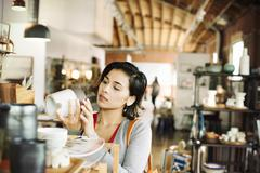 Young woman in a shop, looking at a ceramic jug. Stock Photos