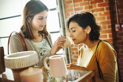 Two young women in a shop, smelling a jar of lavender salve. Stock Photos