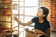 Young woman in a shop, placing a drinking glass on a shelf. Stock Photos