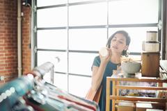 Young woman in a shop, looking at a ceramic mug. Stock Photos