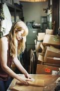 Woman in a shop wrapping merchandise in brown paper. Stock Photos