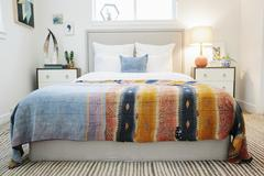 A bedroom and a vivid striped patterned bedspread. Stock Photos