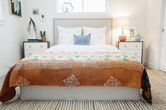Double bed and a vivid patterned bedspread. Stock Photos