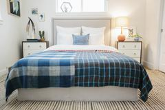 A bedroom in an apartment with a double bed with a colourful checked bed cove Stock Photos