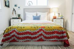 A double bed with patterned retro look bedspread. Stock Photos