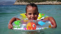 Close up boy swims and turns in air ring Stock Footage