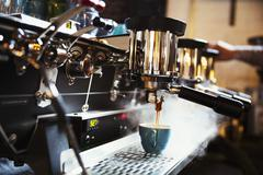 Specialist coffee shop. A coffee machine making coffee. Steam and heat. Stock Photos