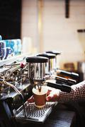 A person working at a large coffee machine, steam heat and pipes Stock Photos