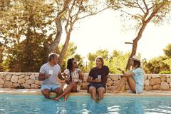 Two couples sit at poolside talking, front view Stock Photos