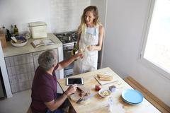 Couple drink wine and prepare food in kitchen, elevated view Stock Photos