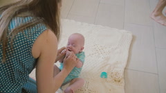 Young mother is trying to lay her baby on the blanket on the floor but he starts Stock Footage