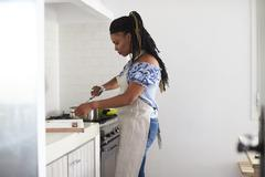 Woman cooking with a saucepan on the hob in her kitchen Stock Photos