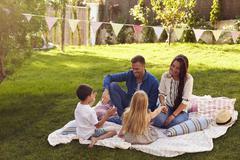 Family Relaxing On Blanket In Garden Stock Photos