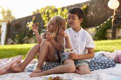 Two Children Enjoying Picnic On Blanket In Garden Stock Photos