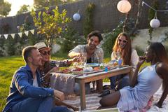 Group Of Friends Enjoying Outdoor Picnic In Garden Stock Photos