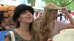 Blonde girls trying on hats at market stall Stock Footage