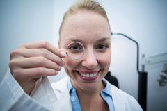 Female optometrist looking through magnifying glass Stock Photos