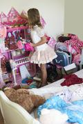 Rear View Of Young Girl Playing With Dolls House In Bedroom Stock Photos