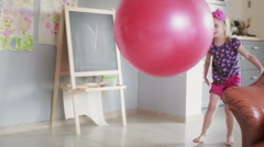 A daughter and her father playing with a gym balloon in their living room Stock Footage