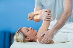 Woman receiving shoulder therapy from physiotherapist Stock Photos