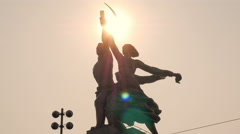 Sun is shining very brightly through sickle and hammer of statue Worker and Stock Footage