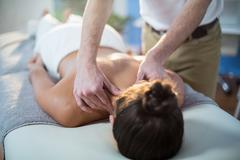 Physiotherapist giving physical therapy to the neck of a female patient Stock Photos