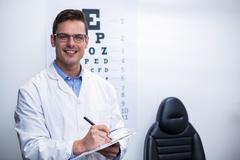 Optometrist writing on clipboard Stock Photos