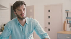Young man in a blue shirt is having a conversation in the kitchen. Slow motion Stock Footage
