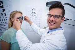 Optometrist examining female patient with phoropter Stock Photos