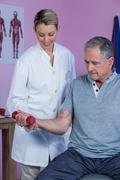 Physiotherapist assisting senior man to lift dumbbell Stock Photos
