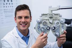 Smiling optometrist adjusting phoropter Stock Photos