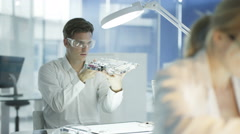 4K Electronics engineers working in lab with man building circuit board Stock Footage