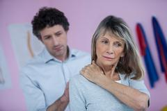 Physiotherapist giving neck massage to female patient Stock Photos