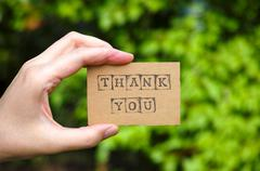 Woman hand holding cardboard card with words Thank You - stock photo