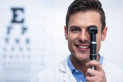 Smiling optometrist looking through ophthalmoscope Stock Photos